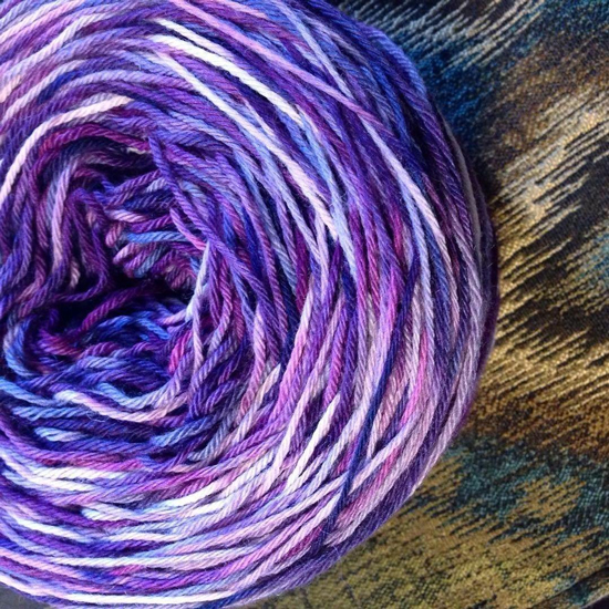 A balled skein of Bijou Basin Ranch's Tibetan Dream Yarn dyed by Miss Babs