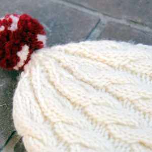 Knit an adorable cable knit beanie for winter with this free pattern.