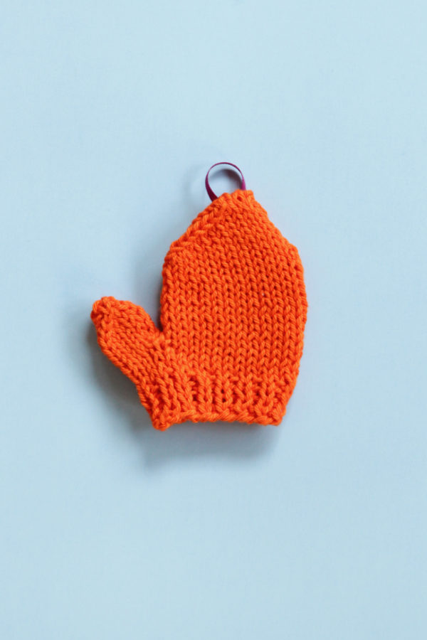 Get a free pattern for this mini knit mitten, which works great for holiday ornaments or as a gift topper!