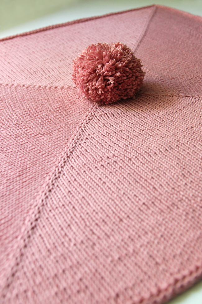 Parlez-vous pom pom? This wee blanket is so adorable, quick and so easy to knit. You'll find yourself cranking out a bunch of these for baby shower gifts galore!