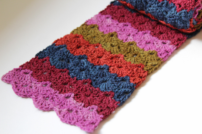 Don't let your favorite scraps go to waste! Crochet the free Scrap Scallops Scarf to elegantly showcase your favorite yarns. Visit handsoccupied.com for the free pattern.