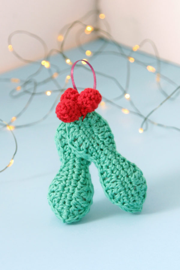 Crochet an adorable holly ornament to hang on your tree for years to come. Get the free pattern for this quick, three dimensional ornament.