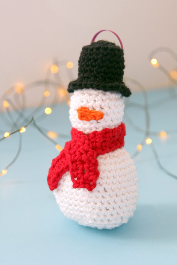 Get a free pattern for this crochet snowman Christmas ornament. Practice your amigurumi skills with this fun pattern!