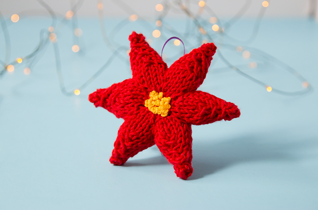 Trim your tree with a hand knit ornament! This festive poinsettia will add a splash of color to your holiday decor. Click through for the free knitting pattern.
