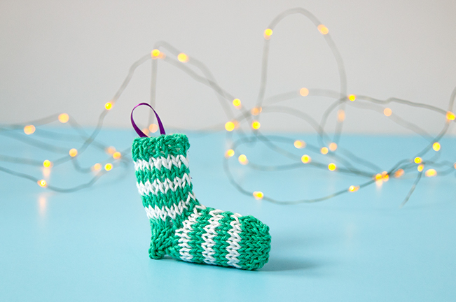 A tiny knit stocking is the most adorable way to trim your tree! Get the free knitting pattern for this striped stocking. #christmasornament #stockingornament #freeknittingpattern