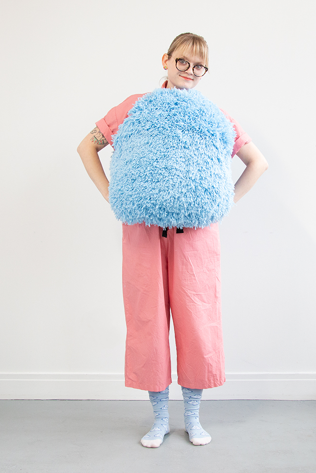 I got this wild idea to make a giant pom pom costume using latch hook, so I gave it a go for Halloween. Take a closer look at this three dimensional rug-making project and its construction.