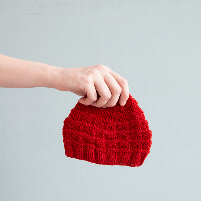 The Triangle Rib Baby Hat knits up so quickly! Get your hands on this free charity knitting pattern for babies on Hands Occupied. #charityknitting #freepattern #babyknitting