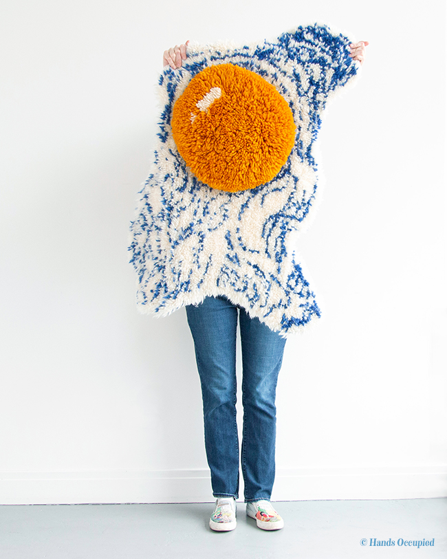 Artist Heidi Gustad models her Fried Egg Wall Hanging, the cover project from her first book, Latch Hook: 12 Projects for the Modern Maker