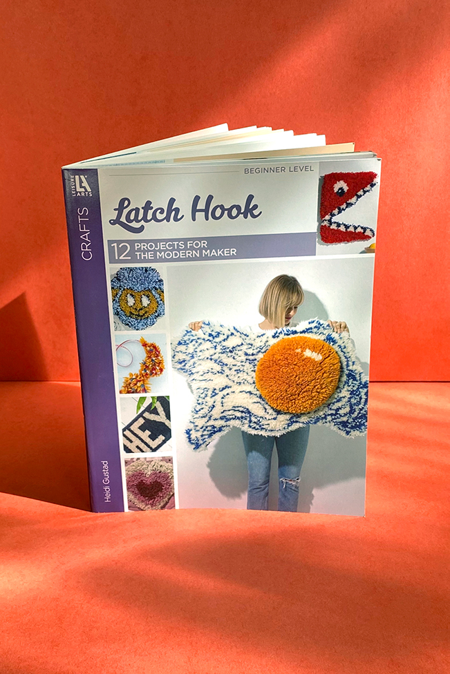 A copy of Latch Hook: 12 Projects for the Modern Maker (2020) by Heidi Gustad on a red background