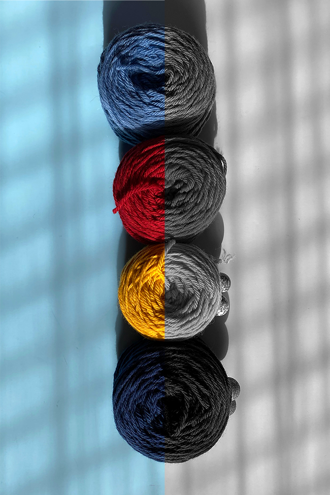 Four skeins of primary colored yarn in color as well as black and white, used to help explain the concept of color value.